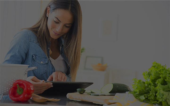 woman working on tablet in kitchen