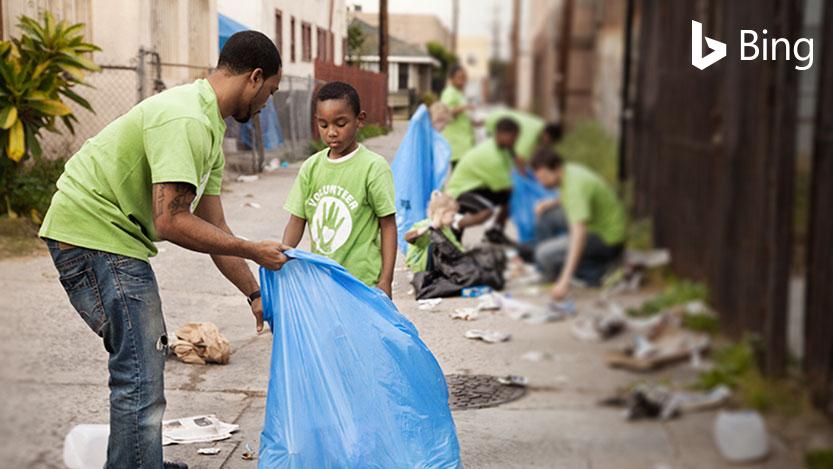 Homme en train d'aider un enfant à ramasser des déchets dans la rue avec un sac poubelle.