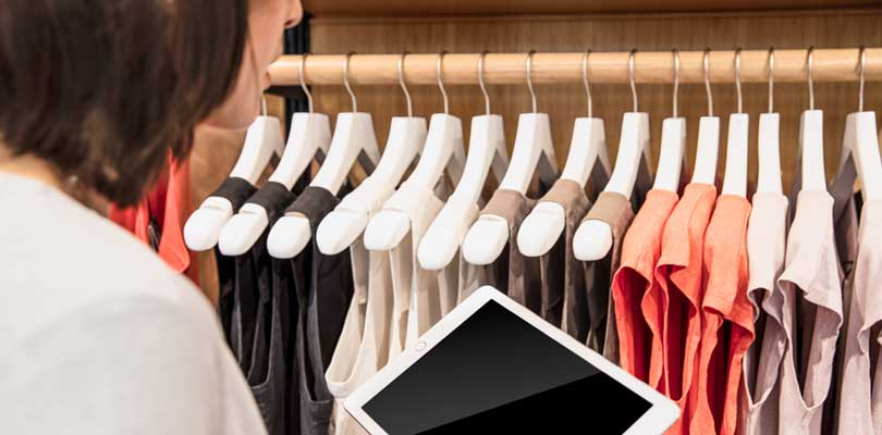 A woman looking at a clothes rack while holding a tablet