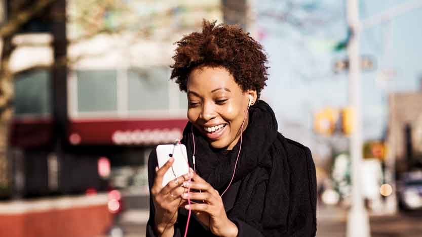A woman laughing and looking at her mobile phone