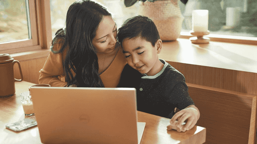 mother and son sitting at a table with a computer together, mother speaking to her son, son playing with a toy car