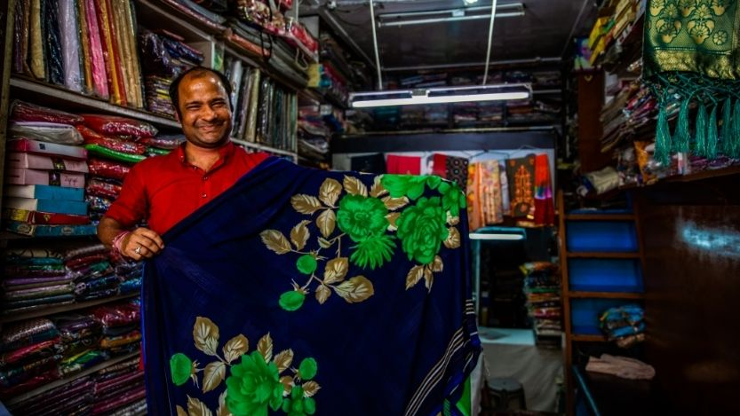 A store owner proudly displays a patterned blue saree for sale in his market stall in Agra, India.