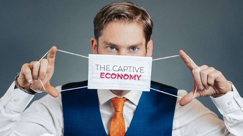 Retail expert Ken Hughes holding mask titled 'The Captive Economy'.