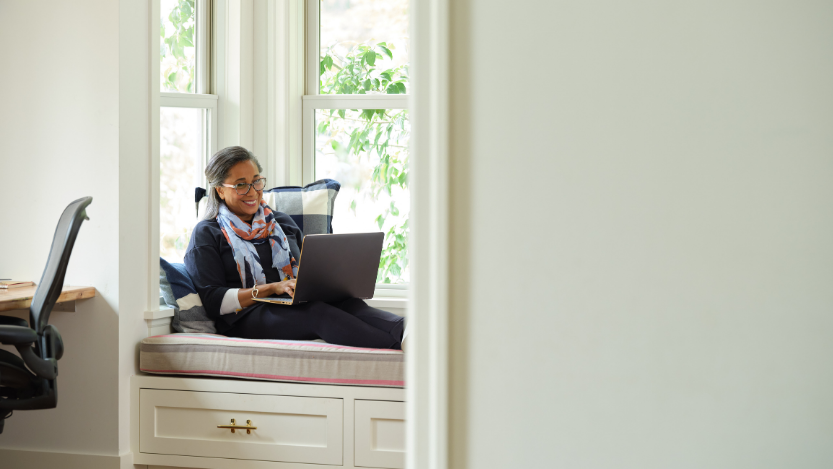 Image of a smiling woman with glasses working on a laptop computer in a cushioned bay window. She is laid back against a big pillow and there is foliage outside the window.