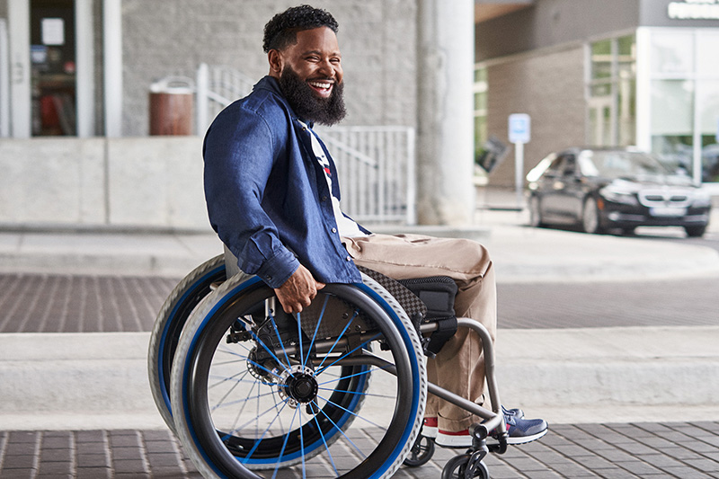 A smiling man in a wheelchair wearing Tommy Hilfiger clothing.