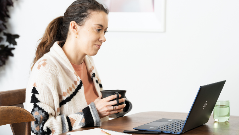 Woman holding a mug with laptop on dining room table with an HP Elite Dragonfly