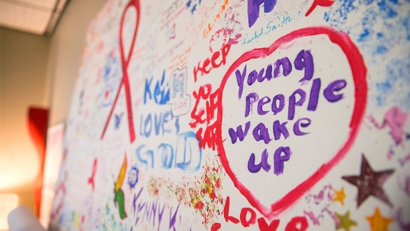 Decorative image of graffiti on a white wall with a focus on one drawing of a heart with 'young people wake up' painted inside.