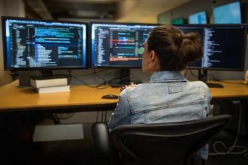 Mujer sentada en un escritorio de trabajo, analizando la información de tres pantallas.