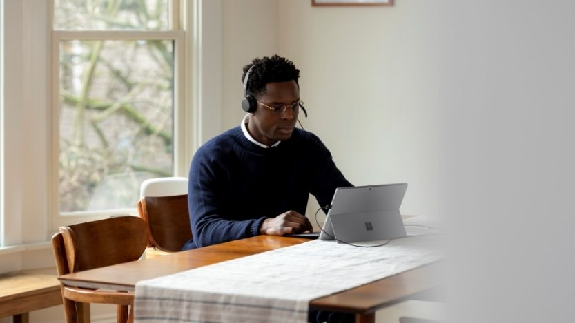 Adult male inside using Microsoft Modern USB Headset and Surface Pro