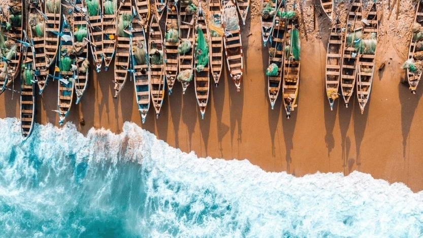 An aerial view of fishing boats on the Cape Coast of Ghana moored on sandy shore while the aqua colored tide breaks near them.