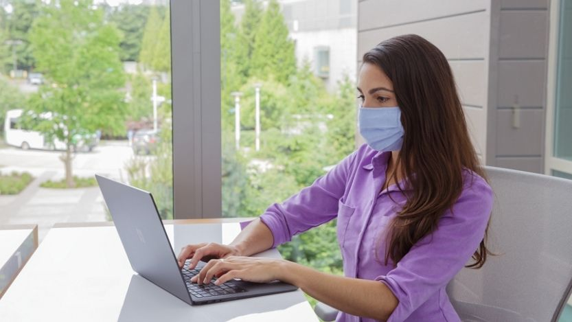 A female employee wearing a face mask working on her Surface laptop at her desk.