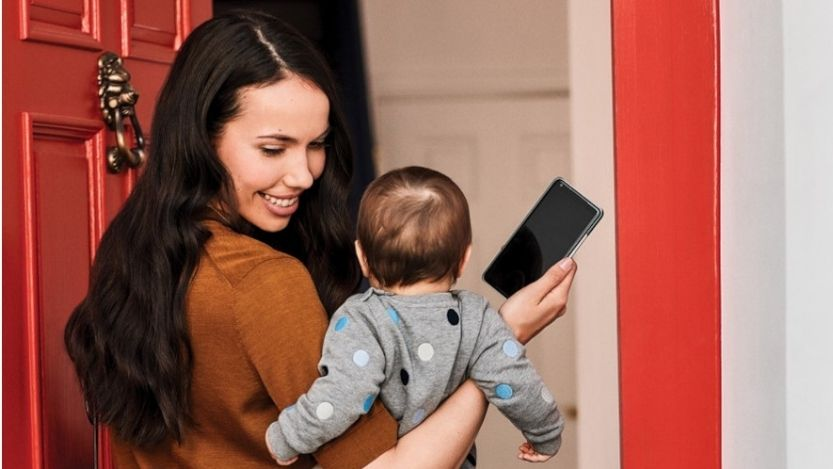 woman holding a baby with a phone in hand.