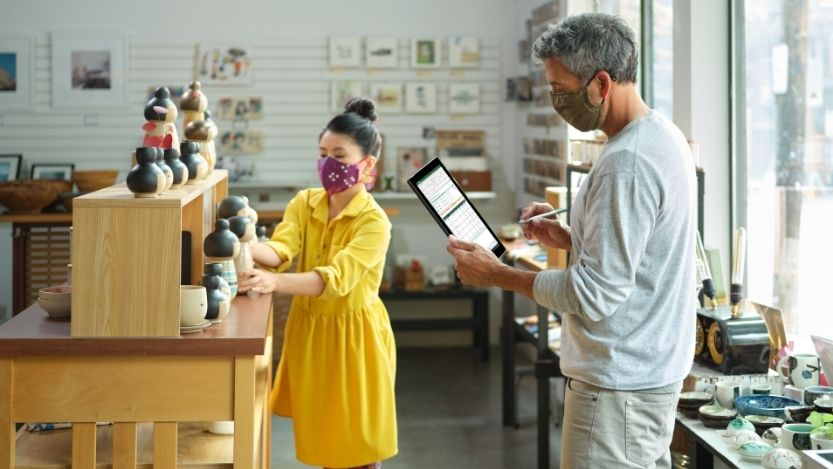 2.Angestellter im Einzelhandel mit Maske, der den Bestand für einen Abholauftrag überprüft.