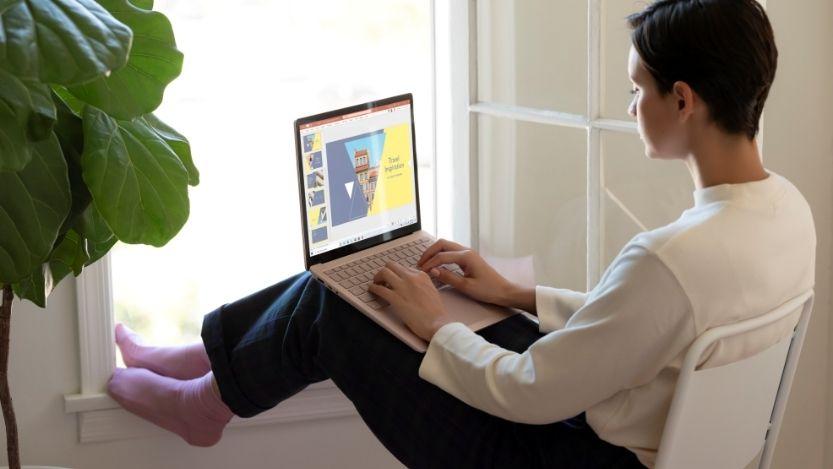 Mujer usando un portátil 3 para editar una presentación en PowerPoint