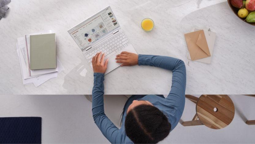 Une femme est assise dans la cuisine et travaille sur son ordinateur portable.