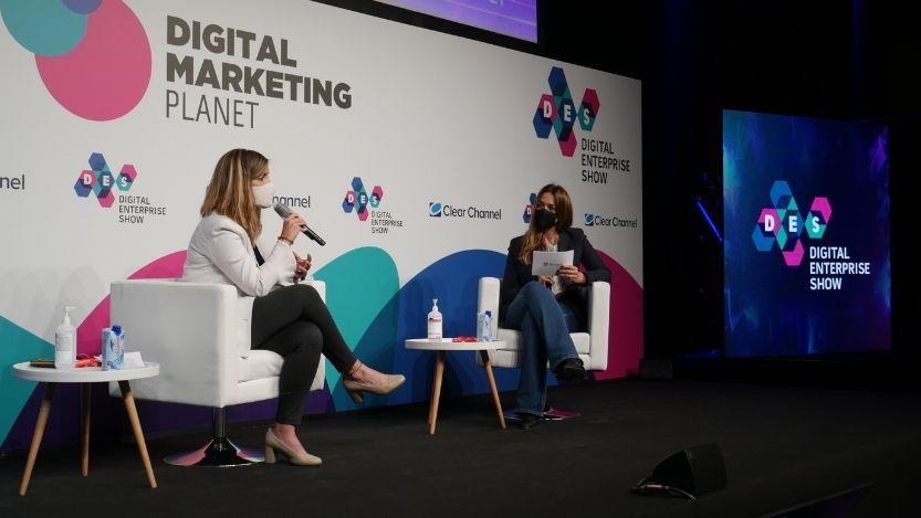 Imagen de dos personas con micrófono sentadas en el escenario del evento.