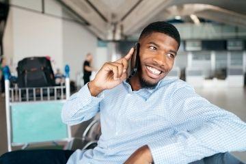 Portrait-eines-jungen-Mannes-der-an-einem-Flughafen-über-ein-Handy-telefoniert