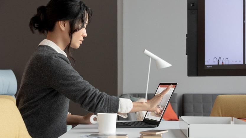 Junge-Frau-mit-schwarzen-Haaren-die-ein-graues-Wollhemd-trägt-an-ihrem-Schreibtisch-sitzt-und-an-ihrem-Laptop-arbeitet.