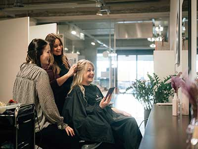 Three woman laughing together at a hair salon.