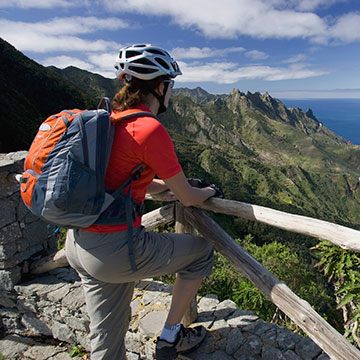 Man wearing a biking helmet and backpack enjoys a mountain view at an overlook.