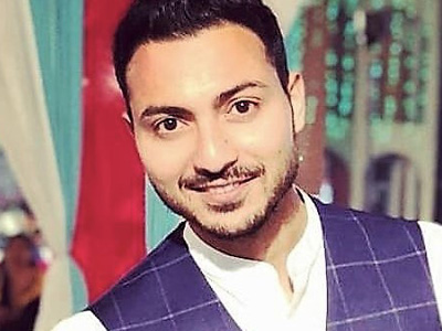 Akshay Sharda, head of digital marketing at EaseMyTrip, stands against a multi-coloured background. He is a medium skinned man with brown hair and trimmed beared wearing a white mandarin collared shirt and navy blue and white checkered vest.