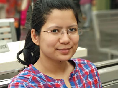 Suvidha Bisht, assistant manager of digital marketing for EaseMyTrip sits in an outdoor area. She is a medium skinned woman with dark brown hair. She wears rectangular wireframe glasses and a red, blue and white plaid cotton shirt.
