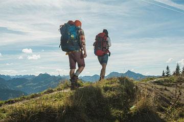 4 Personen in Wanderkleidung stehen auf einer grasbewachsenen Anhöhe und blicken auf die Landschaft