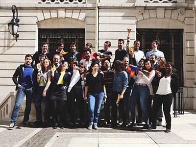 Un groupe multiculturel d'employés de Dolead regardant excités et debout au soleil à l'extérieur de leur bureau à Paris, en France.