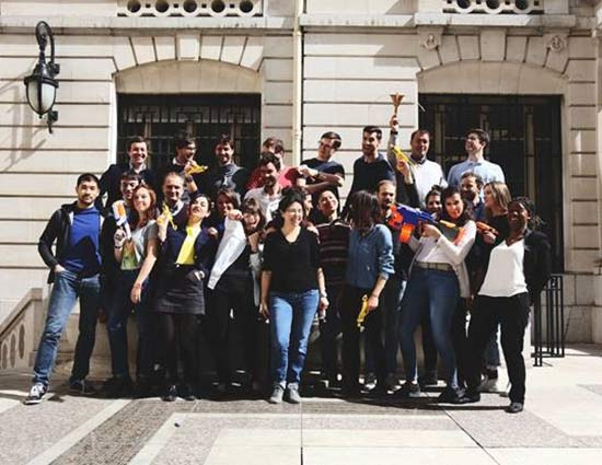 A multicultural group of Dolead employees looking excited and standing in the sun outside their office in Paris, France.