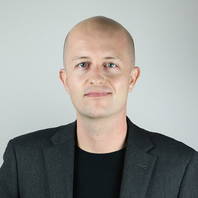 Ryan May, founder and CEO of Concourse Media, stands against a gray background. He is a bald, light skinned man in a navy blue suit jacket and black sweater.