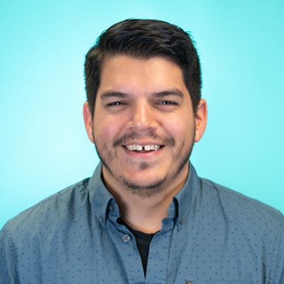 Image of Steve Guzman, a medium complexioned person with short brown hair who is smiling and wearing a blue Oxford shirt.